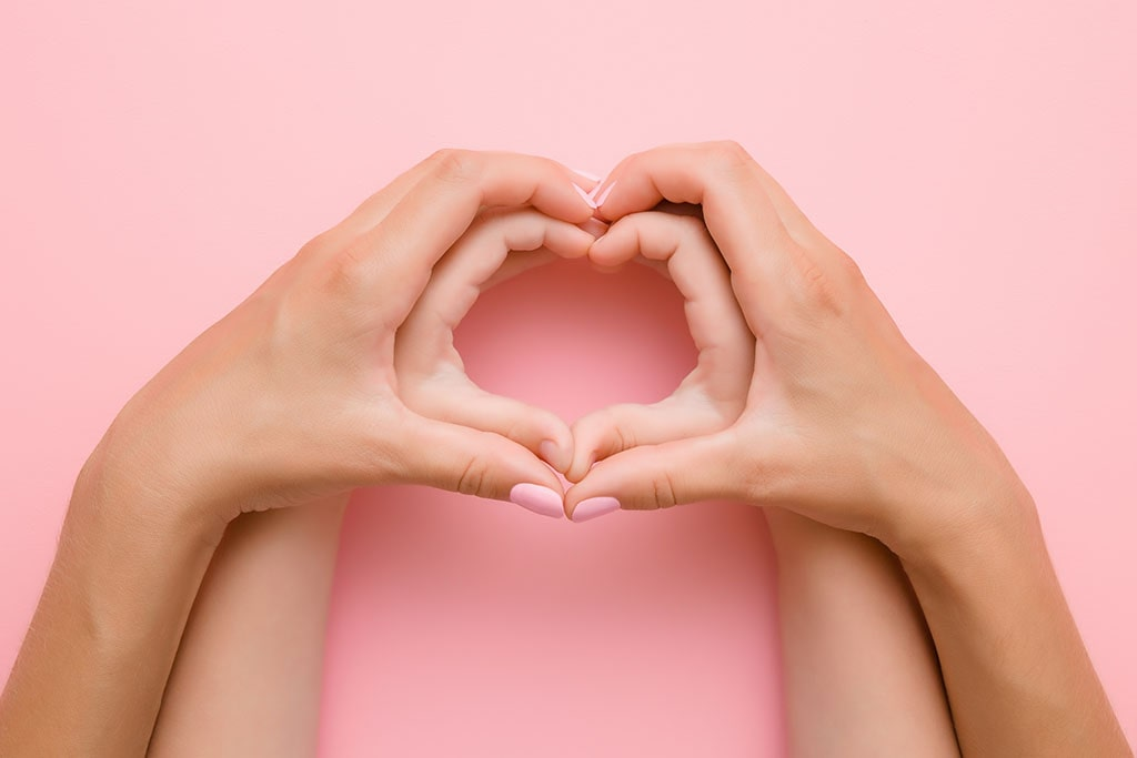 heart shaped hands on pink background
