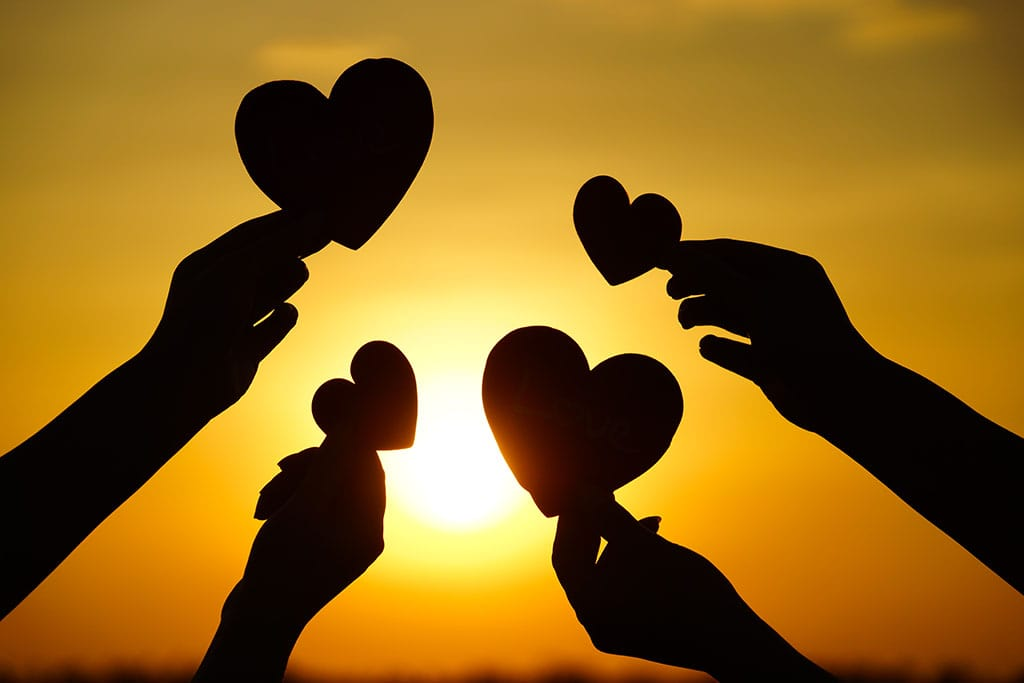 hands holding hearts up to the sun