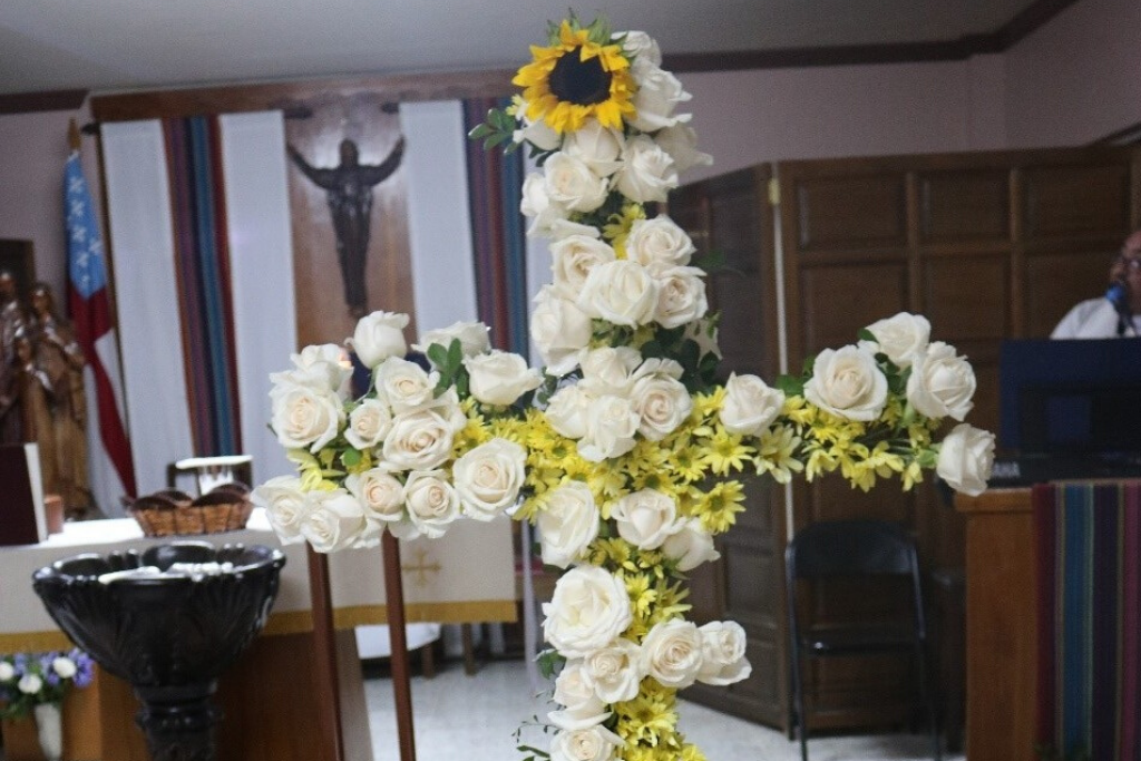 A Cross that's covered by yellow flowers