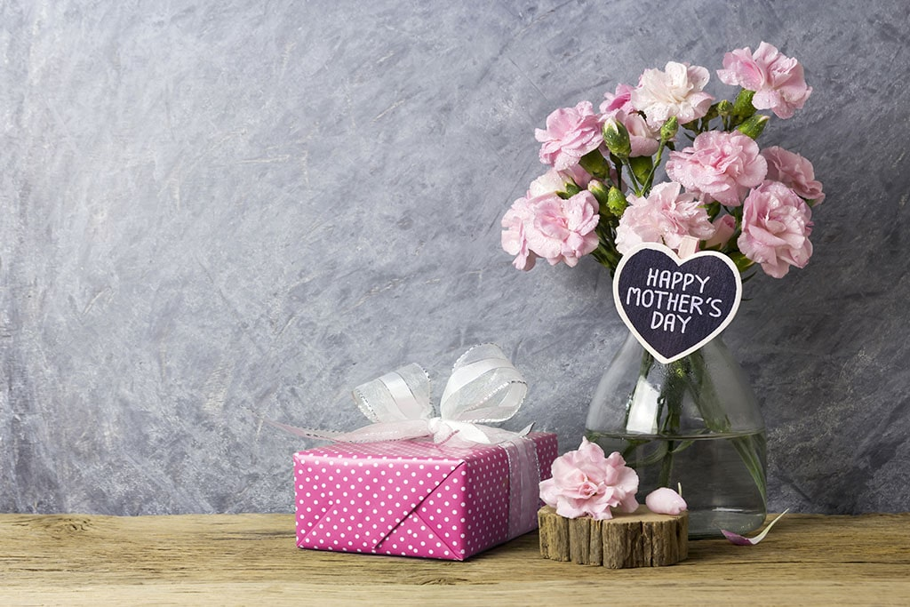 Vase of Mother's Day roses with present