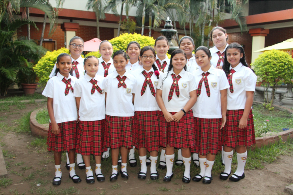 A group of girls in red and white uniforms from the Escuela Madre Maria Luisa