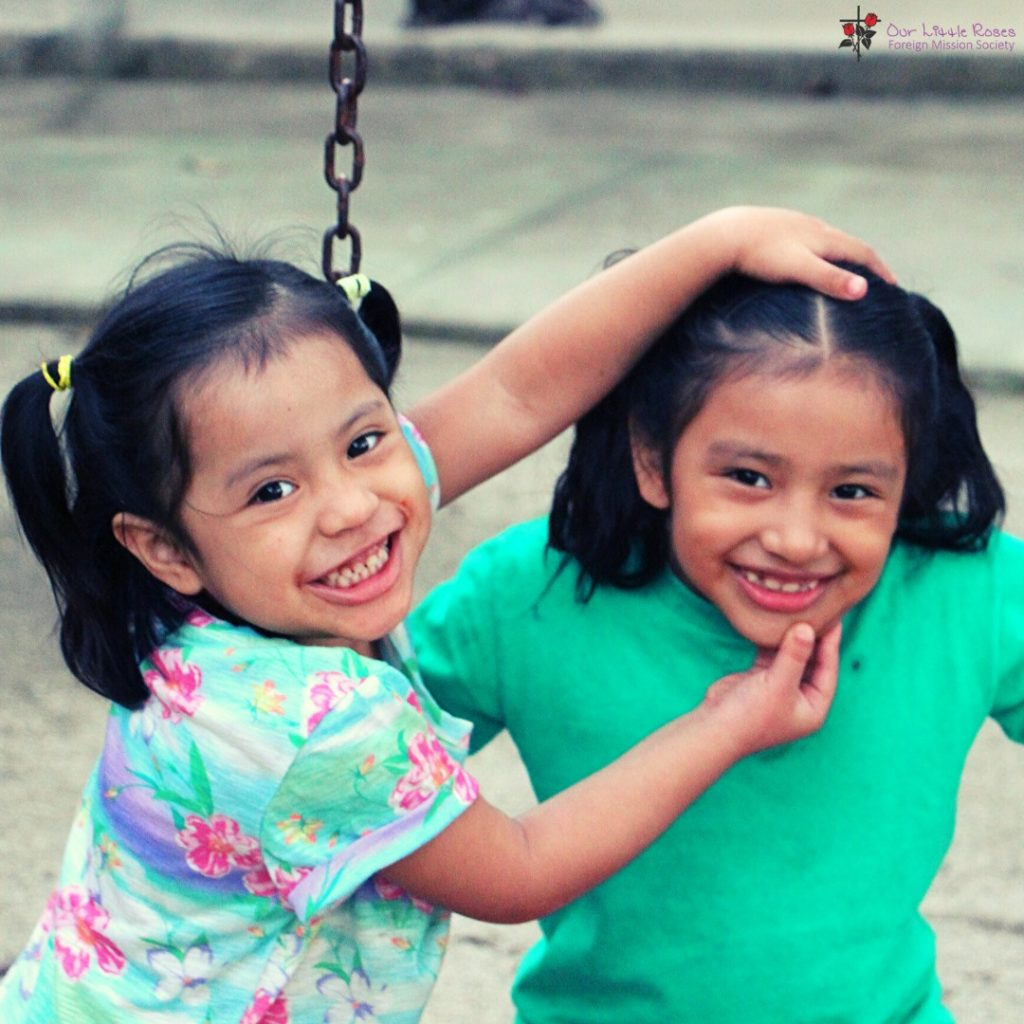 Two young girls smiling at a playground