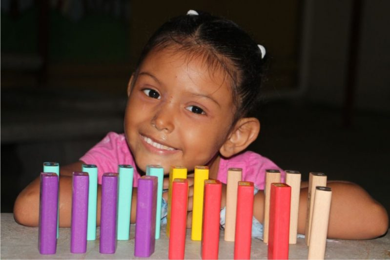 A young Honduran girl at school with colorful educational blocks