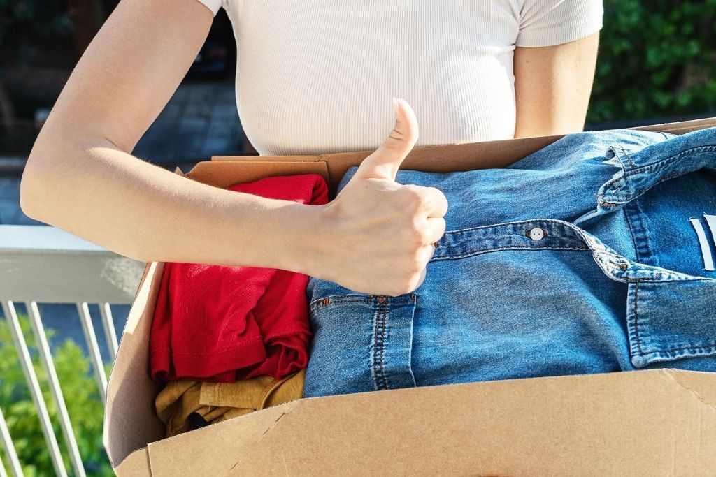 Woman holding a box of used clothing.