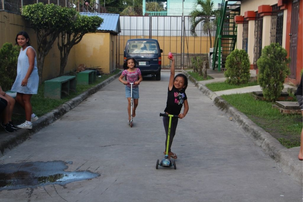 Two girls from Our Little Roses riding on scooters