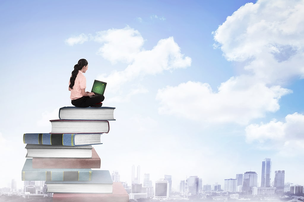 Woman sitting on top of a large pile of books facing the sky