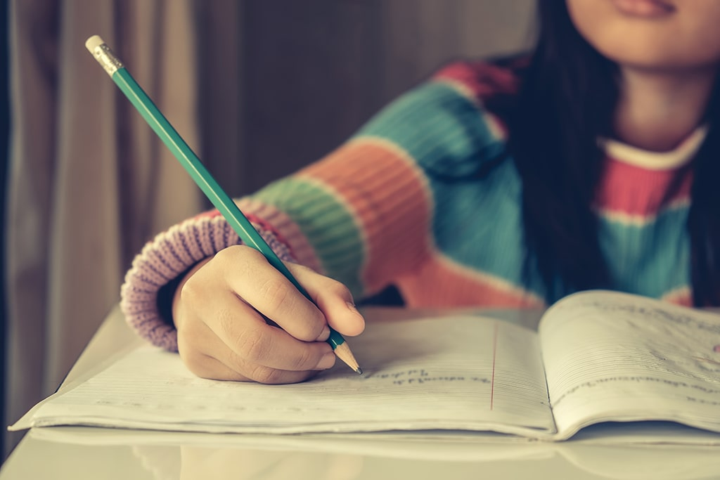 Young child in multicoloured top writing