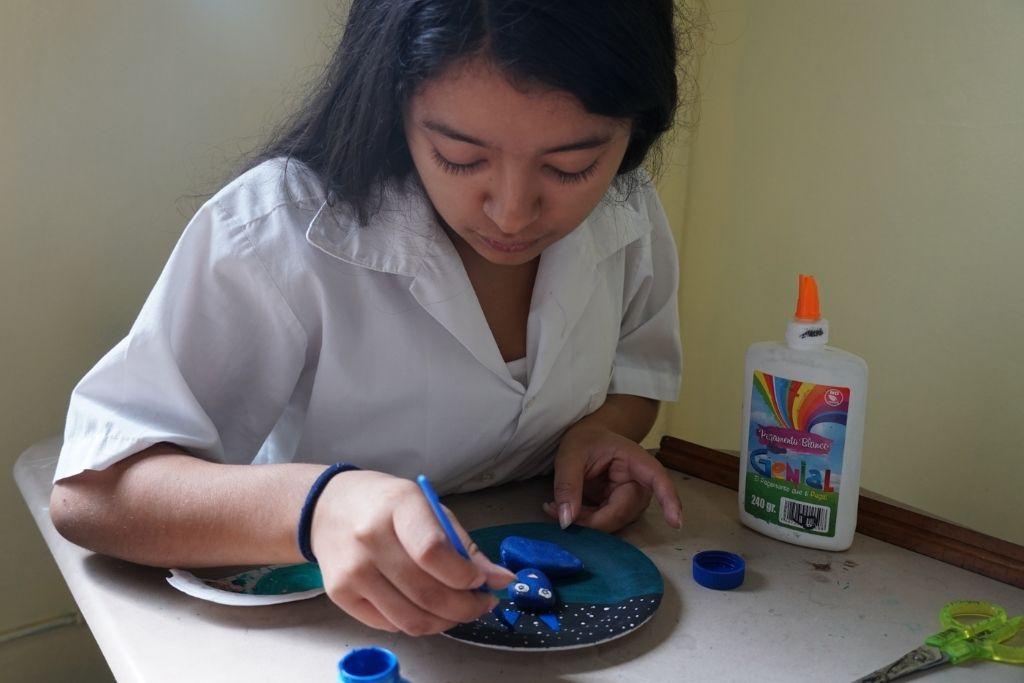 A girl painting a plate as a form of expressive arts therapy