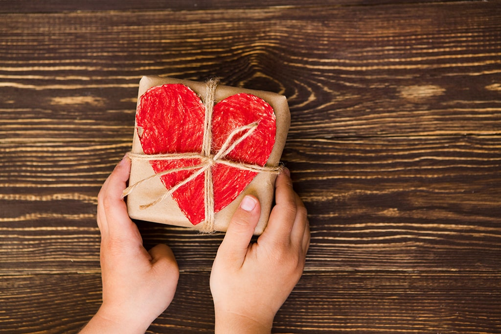 hands holding box with heart on it