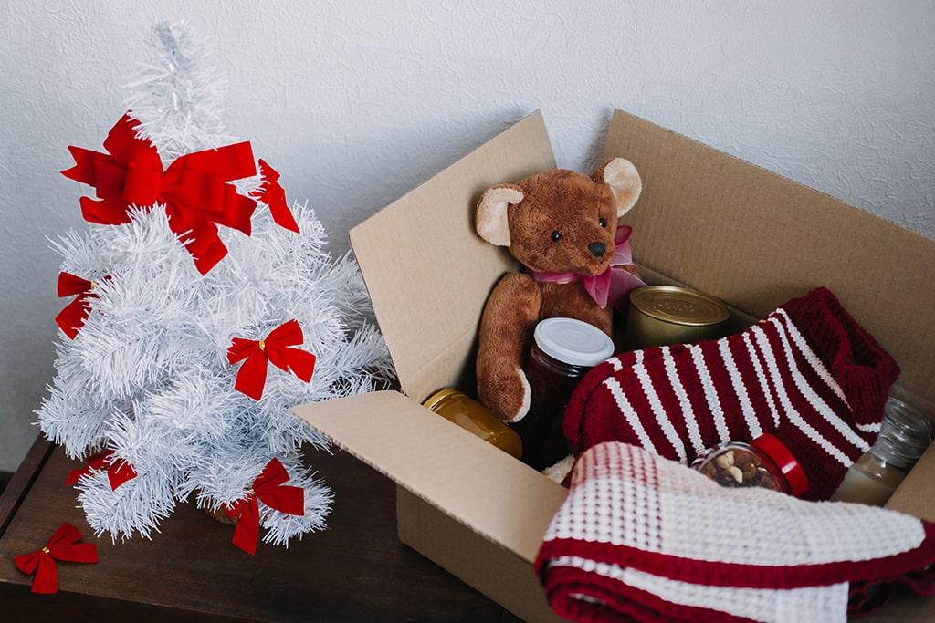 Donation box full of toys next to white Christmas tree