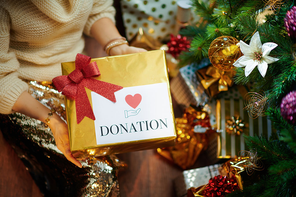 Closeup on elegant middle age housewife in gold sequin skirt and white sweater under decorated Christmas tree near present boxes holding special Christmas charity gift box.