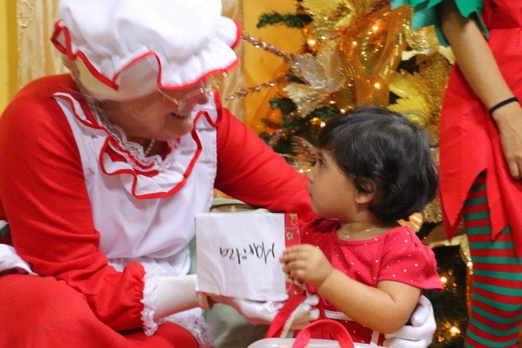 A young Honduran girl with Mrs. Claus during a Christmas celebration.