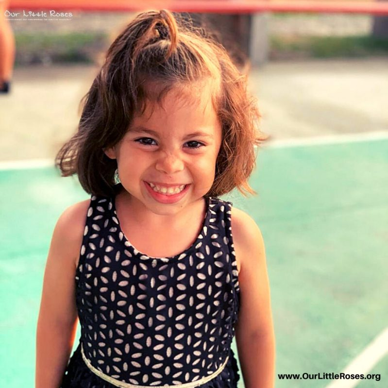 A young Honduran girl smiling at the camera while standing outside