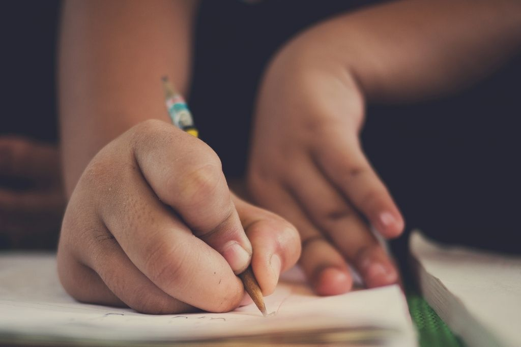 A child writing in a notebook for their school assignment