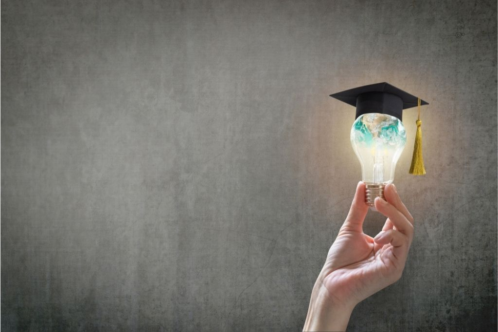 A hand holding a lightbulb with a globe inside of it that has a graduation cap on top.