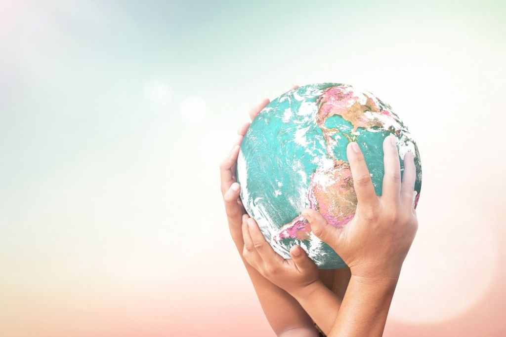 Childrens' hands holding a globe.