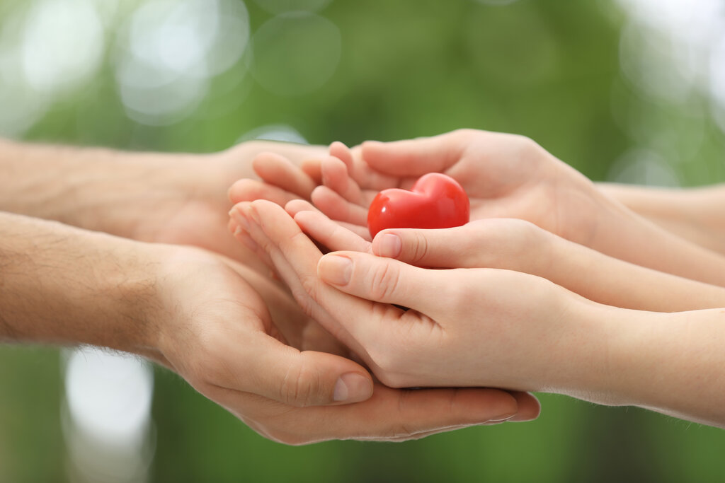 Adult and child linking hands with heart in the middle