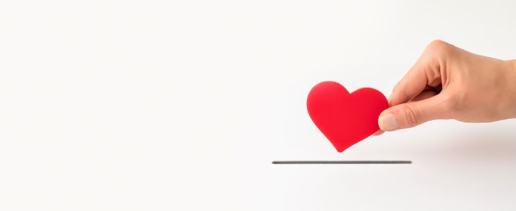 A hand holding onto a heart with a white background.