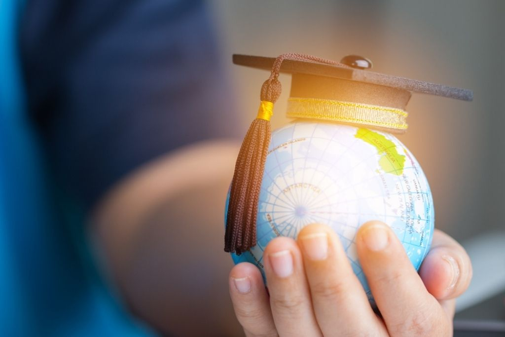 Child holding a small light-up globe with a graduation cap on top.