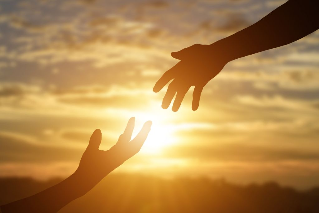 Two hands reaching out to help one another with a sunset in the background
